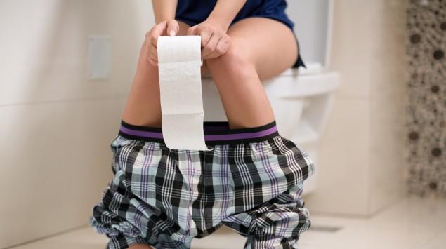 Eine Frau sitzt auf der Kloschüssel und hält eine Rolle Toilettenpapier in den Händen.