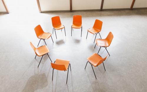 Stuhlkreis aus orangen Stühlen