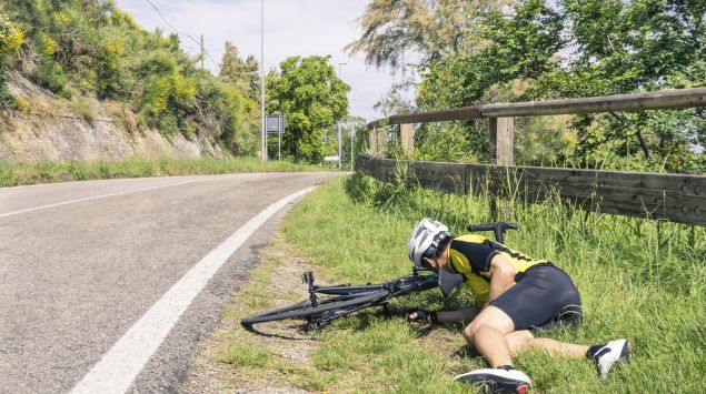 Ein Fahrradsportler ist gestürzt und liegt neben seinem Rad am Straßenrand.