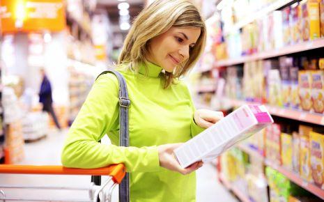 Clean Eating: Eine Frau betrachtet im Supermarkt die Verpackung einer Ware genauer.
