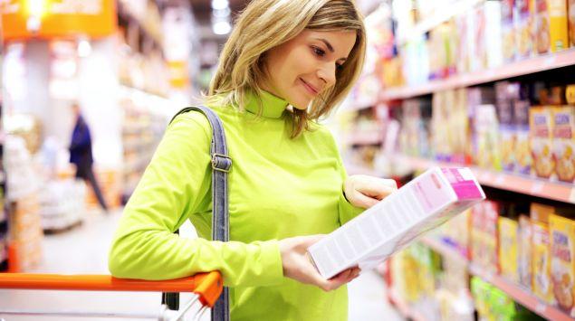 Eien Frau betrachtet im Supermarkt die Verpackung einer Ware genauer.