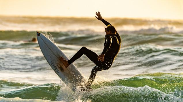 Ein Mann surft im Meer.