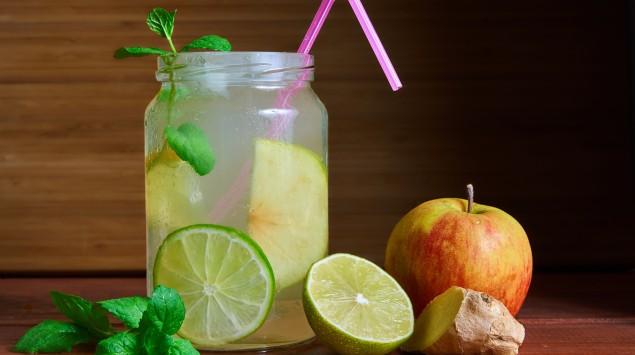 Man sieht einen Switchel im Glas mit Apfel, Ingwer und Zitrone.
