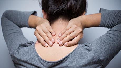 Das Bild zeigt eine Frau, die ihren Nacken hält.