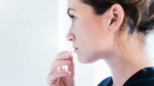 Eine ernst dreinblickende Frau führt eine Tablette zum Mund.