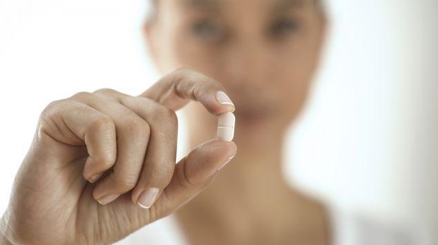 Eine Frau hält eine Tablette in die Kamera.