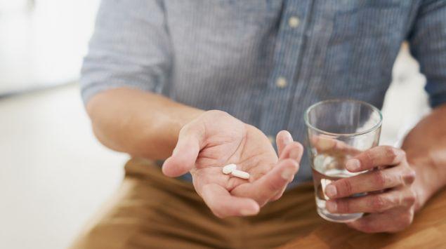 Ein Mann hält zwei Tabletten in der rechten Hand und ein Glas Wasser in der linken Hand.