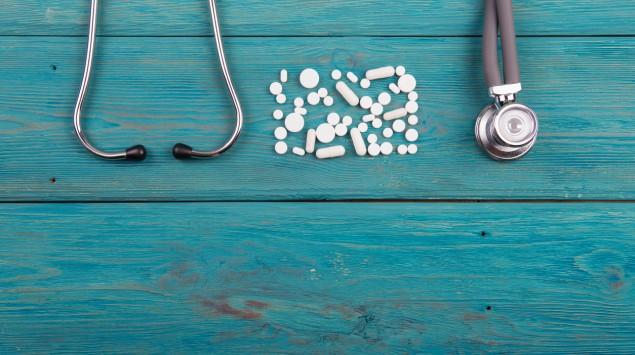 Tabletten und ein Stethoskop auf blauem Holzhintergrund.