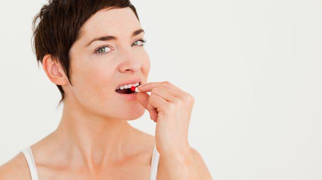 Eine Frau steckt sich eine Tablettenkapsel in den Mund.