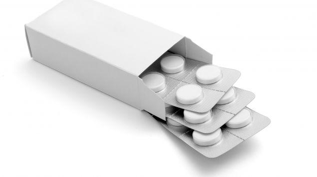 Man sieht eine weiße Pappschachtel mit weißen Tabletten.