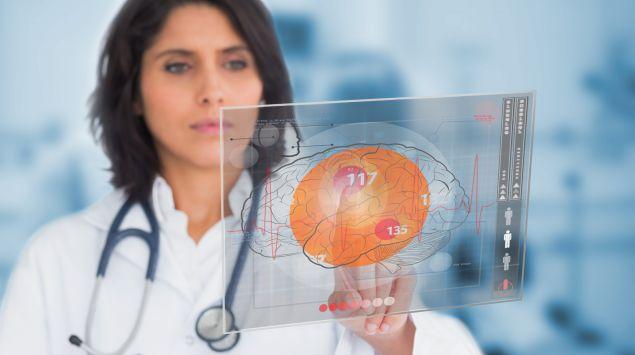 Eine Ärztin studiert eine Tafel, auf der ein Gehirn abgebildet ist.