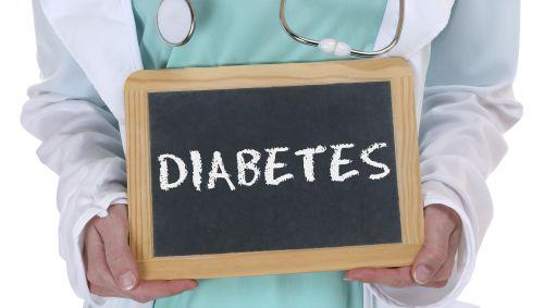Ein Arzt hält eine Tafel mit dem Schriftzug Diabetes in den Händen.