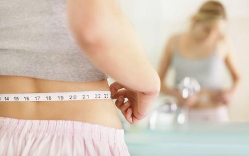 Eine Frau misst den Umfang ihrer Taille mit einem Maßband.