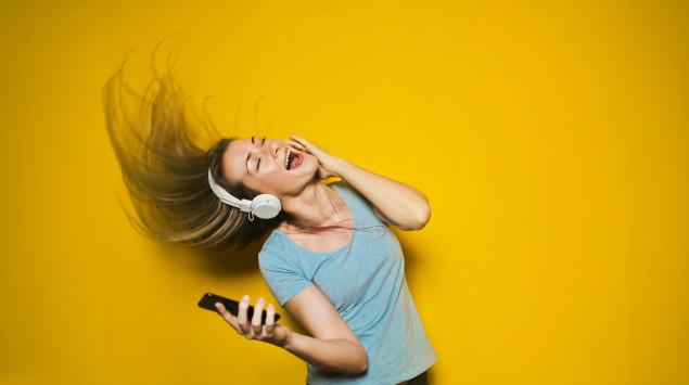 Eine Frau hat Kopfhörer auf und tanzt vor gelbem Hintergrund.