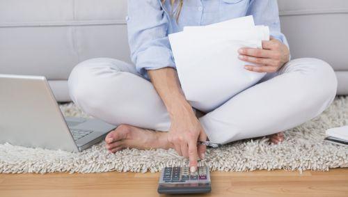 Eine Frau sitzt auf dem Boden und tippt etwas in einen Taschenrechner ein.