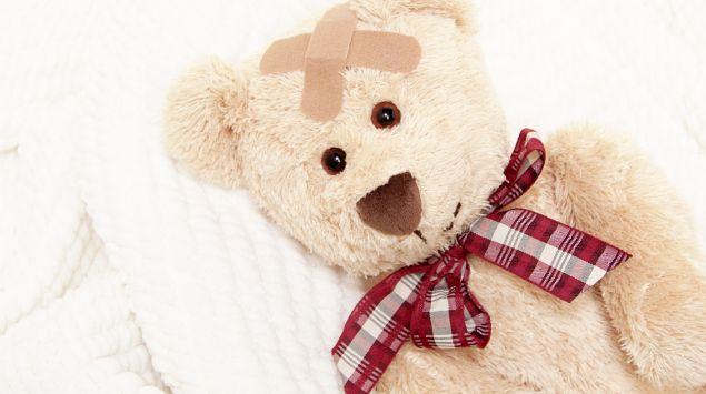 Ein Teddy mit Pflaster auf dem Kopf liegt im Bett.