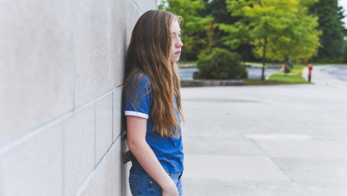 Ein Mädchen in der Pubertät steht einsam auf dem Schulhof.