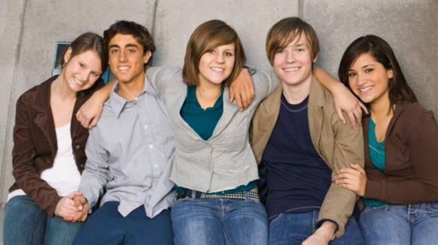 Eine Gruppe Teenager steht eng zusammen.