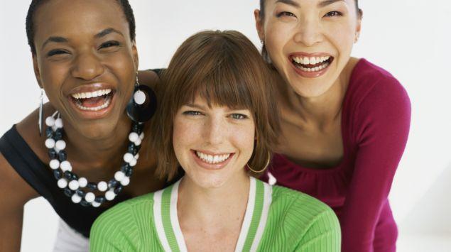 Eine afrikanische, eine europäische und eine asiatische Frau lachen in die Kamera