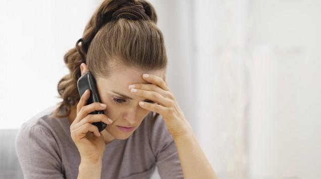 Eine junge Frau telefoniert mit sorgenvoller Miene.