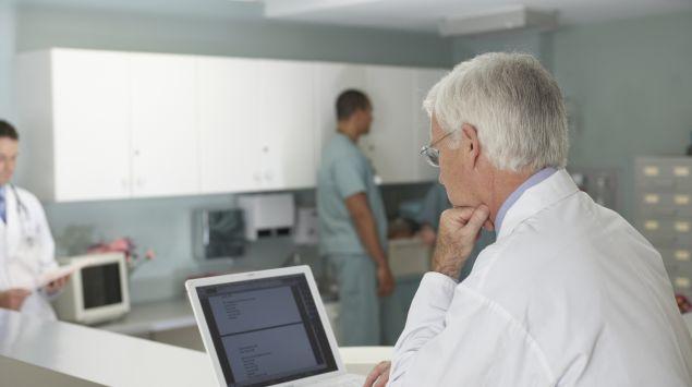 Das Bild zeigt einen Arzt, der an seinem Laptop sitzt.