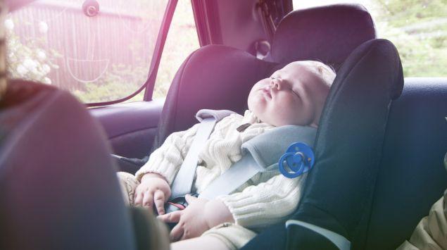 Ein Baby schläft in der Autoschale in der Sonne.