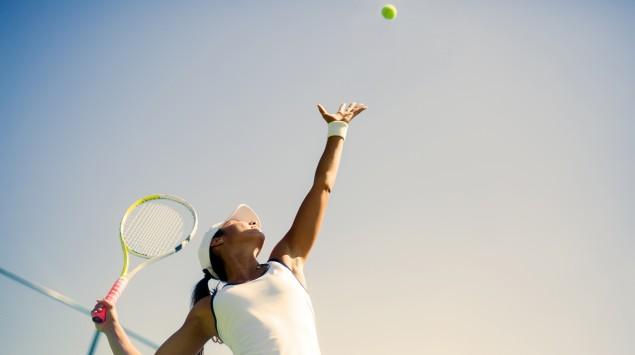 Frau schlägt beim Tennis auf