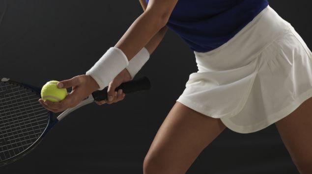 Eine Frau kurz vor dem Aufschlag beim Tennis.