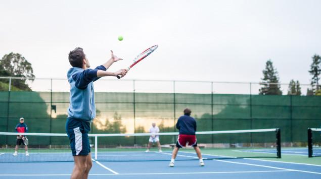 Man sieht Menschen, die auf einem Tennisplatz Tennis spielen.