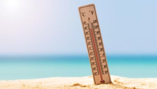 Ein Thermometer steckt im Sand am Strand und zeigt ca. 40 Grad an.