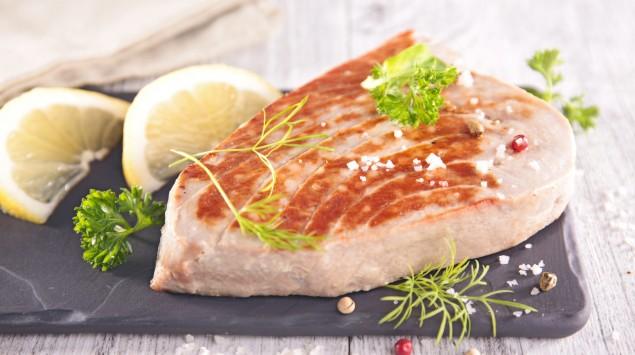 Auf einem Holztisch liegt eine Servierplatte mit einem Thunfischfilet, garniert mit Zitronenstücken, Kräutern udn Gewürzen.