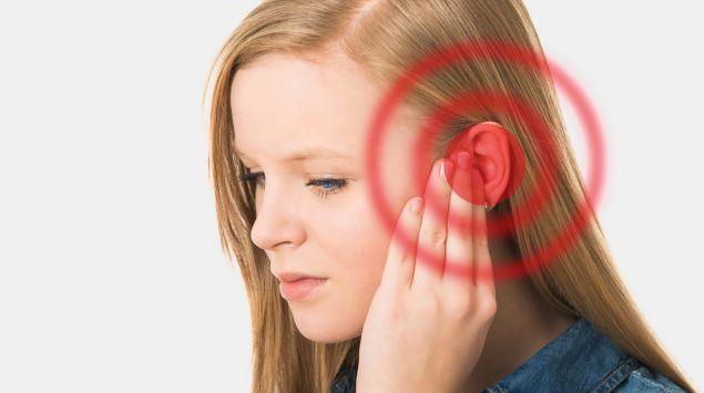 Eine junge Frau drückt ihre Hand aufs Ohr.