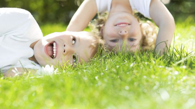 Zwei Kinder toben in der Wiese.