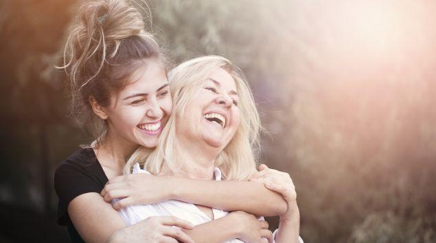 Mutter und Tochter umarmen sich und lachen.