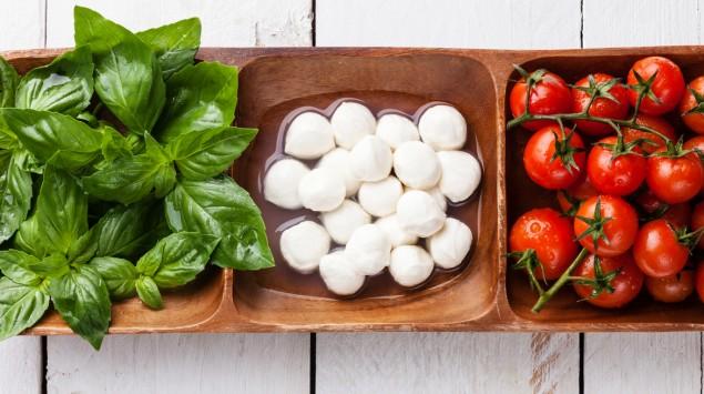 Das Bild zeigt Tomaten mit Mozzarella und Basilikum.