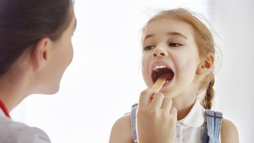 Ärztin untersucht Mädchen auf Mandelentzündung.