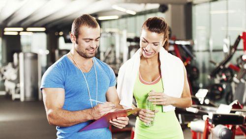 Das Bild zeigt einen Fitnesstrainer mit einem Trainingsplan in der Hand.