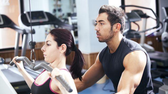 Das Bild zeigt eine junge Frau, die unter Anleitung eines Trainers trainiert.