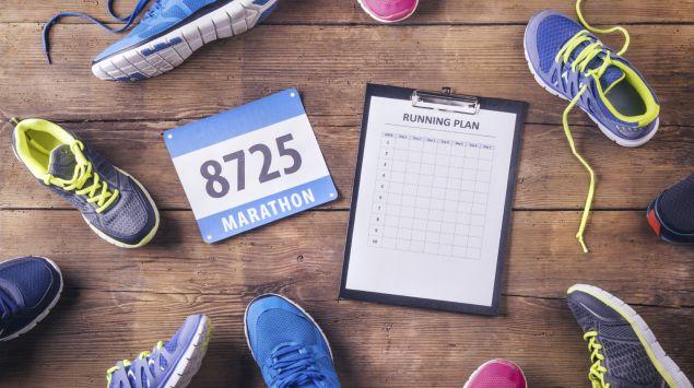 Das Bild zeigt viele verschiedene Laufschuhe auf einem Holzboden. In der Mitte befindet sich ein Trainingsplan.