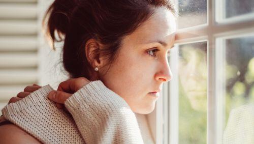Eine traurig aussehende Frau schaut aus dem Fenster.