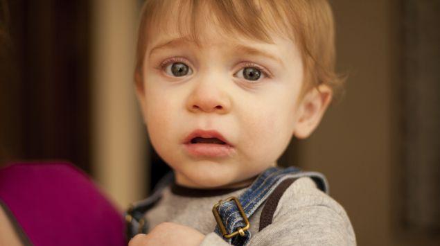 Das Bild zeigt einen traurigen kleinen Jungen.