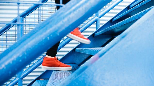 Ein Mensch mit roten Schuhen steigt eine blaue Treppe hinauf.
