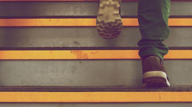 Das Bild zeigt die Schuhe eines Mannes, der gerade eine Treppe hinausgeht.