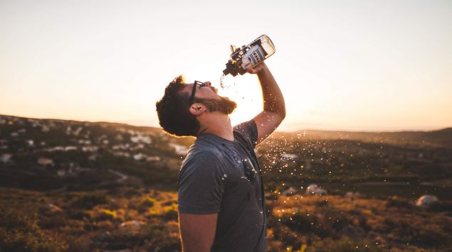 Das Bild zeigt einen Mann, der einen Schluck Wasser aus einer Flasche nimmt.