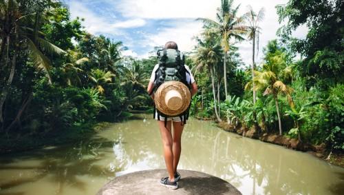 Eine Frau steht mit Wanderrucksack vor einem tropischen Gewässer.