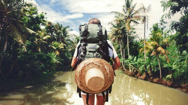 Man sieht eine Frau bei einer Wanderung in den Tropen.
