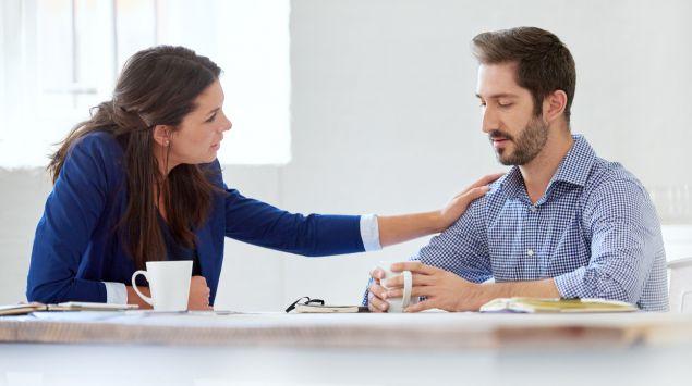 Eine Frau legt einem Mann tröstend den Arm auf die Schulter.