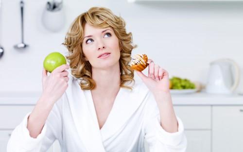 Das Bild zeigt eine Frau, die einen Apfel und einen Muffin in der Hand hält.