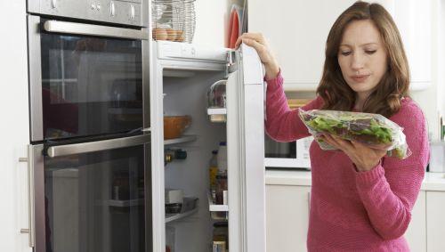 Eine Frau blickt kritisch auf eine Packung Salat, die sie gerade auch dem Kühlschrank geholt hat.