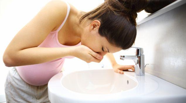 Schwangere Frau übergibt sich ins Waschbecken.